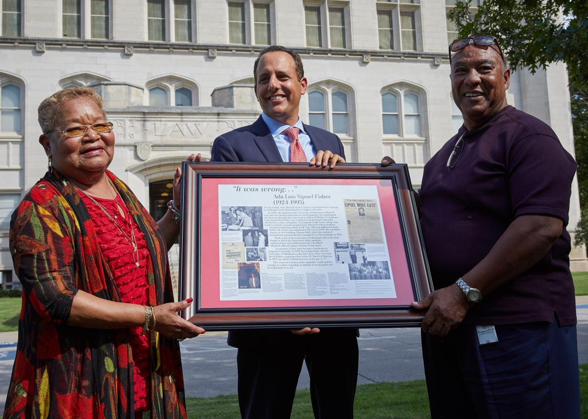 OU Interim President Joseph Harroz Jr. presents to Charlene Factory and Bruce Fisher a framed replica of the display in Monnet Hall that honors their mother, Ada Lois Sipuel Fisher.